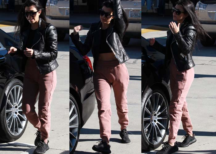 Kourtney Kardashian in a cropped top and pants by Yeezy, which she wore underneath a jacket from Balenciaga