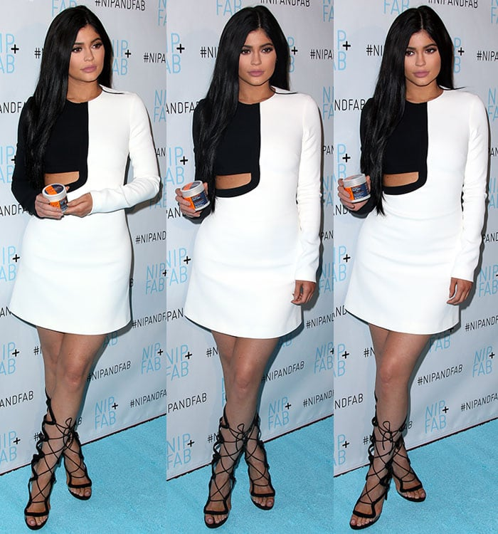 Kylie Jenner poses with Nip + Fab products on the aqua carpet