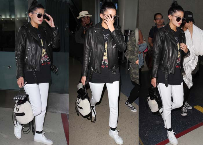 Kylie Jenner arrives at LAX wearing a leather jacket overtop a Yeezy shirt