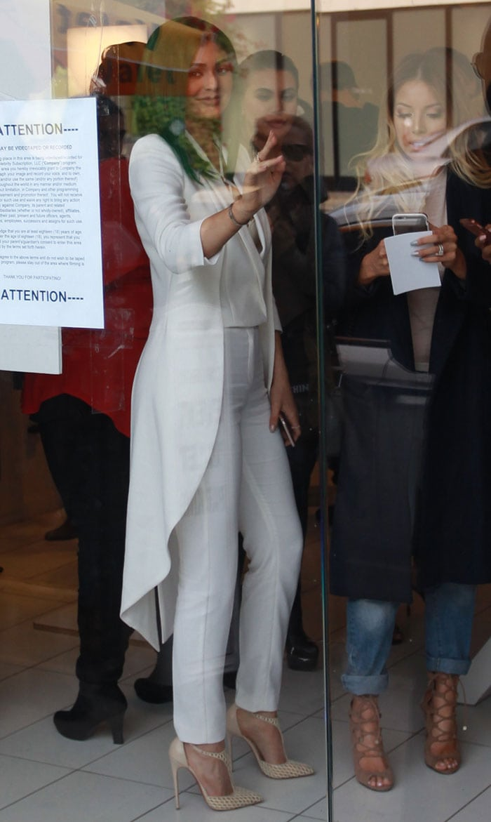 Kylie Jenner wears an all-white ensemble and waves at fans during the launch of her lip kit collection in West Hollywood