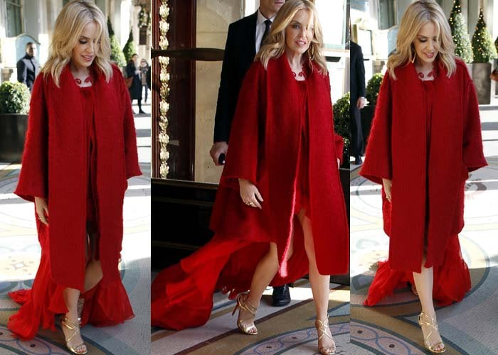 Kylie Minogue wears a red coat over a red dress as she leaves her Paris hotel