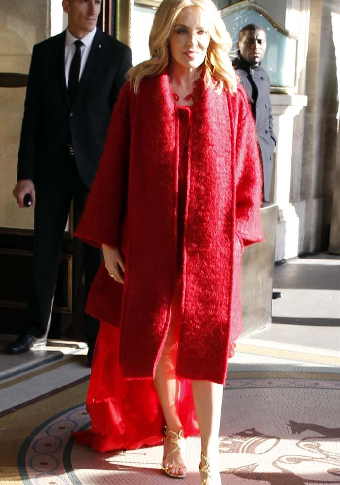 """Kylie Minogue wears a red coat and a red dress with a gold pair of """"Lang"""" heels"""