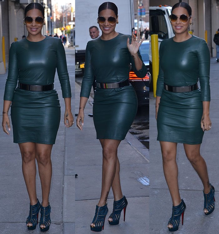 La La Anthony waves while wearing a skintight leather dress