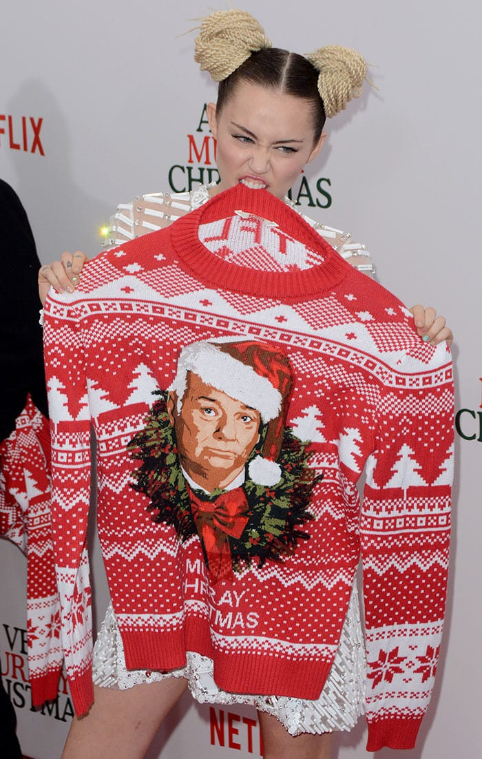 """Miley Cyrus poses with a Bill Murray Christmas-themed sweater at the premiere of """"A Very Murray Christmas"""""""
