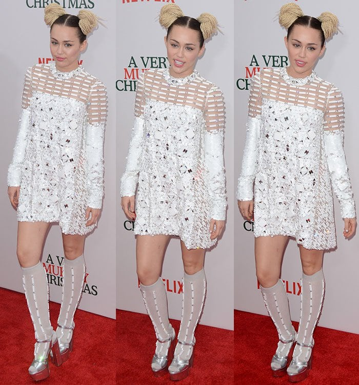 Miley Cyrus poses in a Prada ensemble on the red carpet of a Netflix premiere