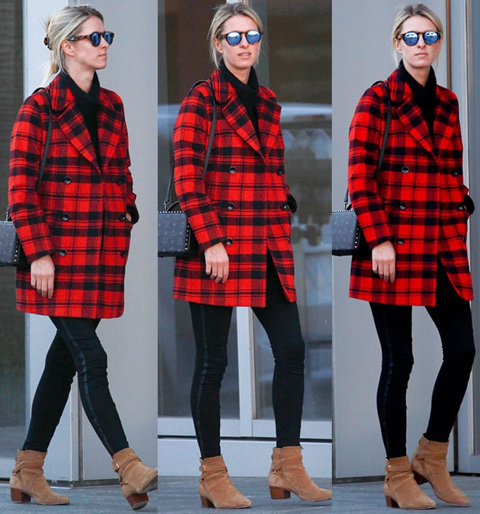 Nicky Hilton wears a red-and-black plaid coat with black leggings and a pair of Saint Laurent booties