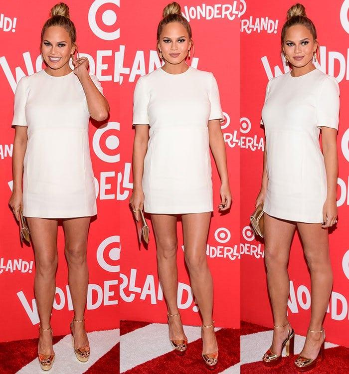 Chrissy Teigen wears a Victoria Beckham dress with a pair of gold heels