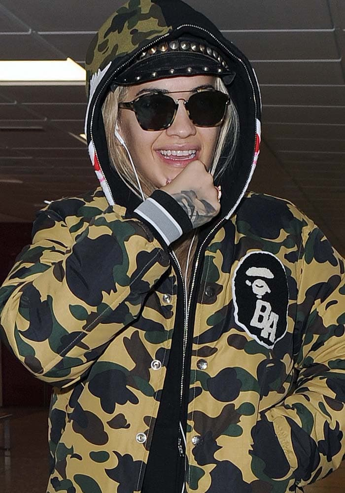 Rita Ora ditches the makeup and hides her hair under a hat as she arrives at London's Heathrow Airport