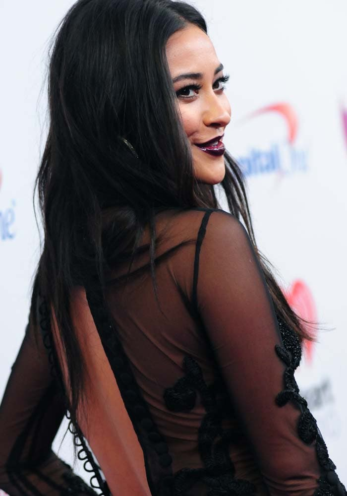 Shay Mitchell shows off her heavy eye makeup and dark lipstick