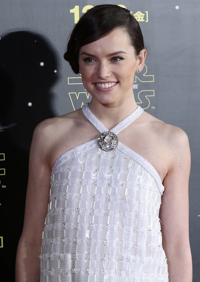 Daisy Ridley with aside bun hairstyle in awhite embellished halter top