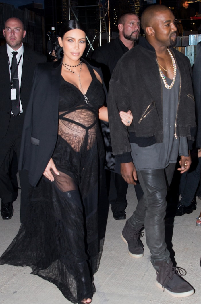 A pregnant Kim Kardashian wears a lingerie dress and thigh-high boots for the Givenchy Runway show at New York Fashion Week