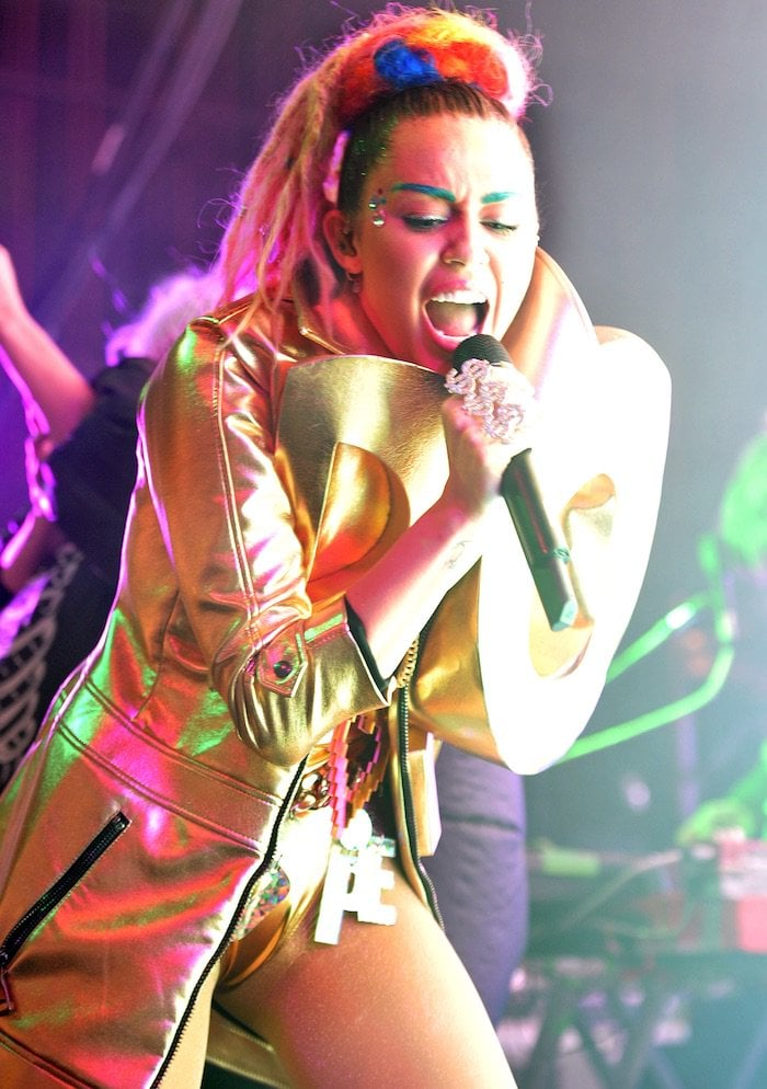 Miley Cyrus wears faux blonde dreadlocks in her hair during a performance at Chicago's Riviera Theatre