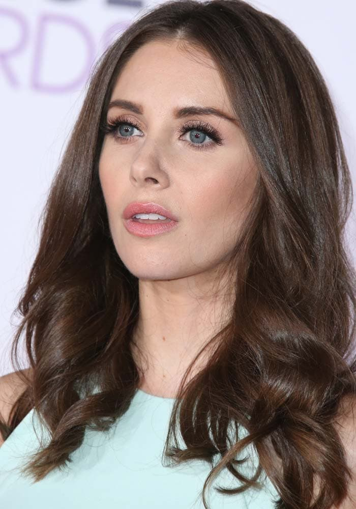 Alison Brie wears heavy makeup and wears her chestnut hair down and loosely curled