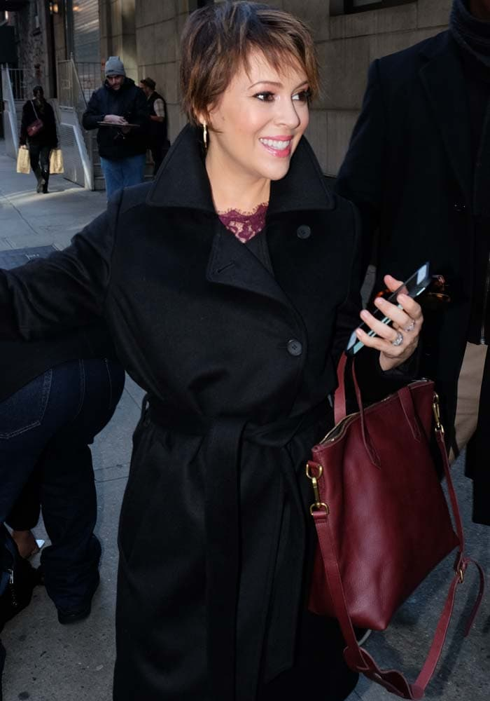 Alyssa Milano smiles at fans as she wears a heavy black coat and carries a burgundy tote
