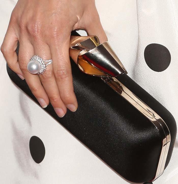 America Ferrera holds a black clutch on the red carpet