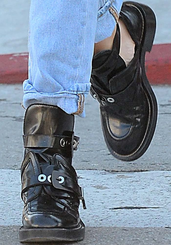 Ashley Benson wears a pair of buckled black boots from Balenciaga