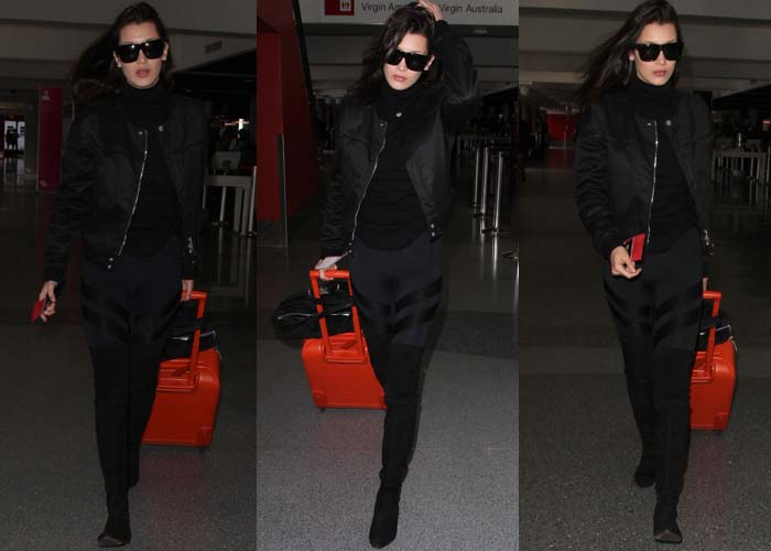 Bella Hadid departs from LAX in an all-black ensemble with a bright orange suitcase