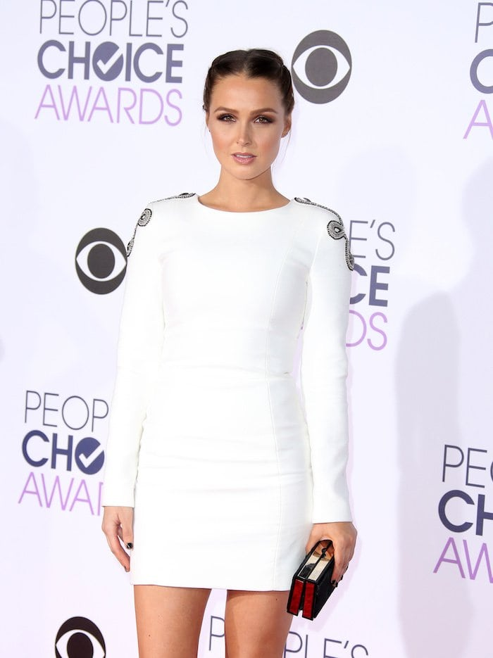 Camilla Luddington holds a Jimmy Choo clutch on the red carpet