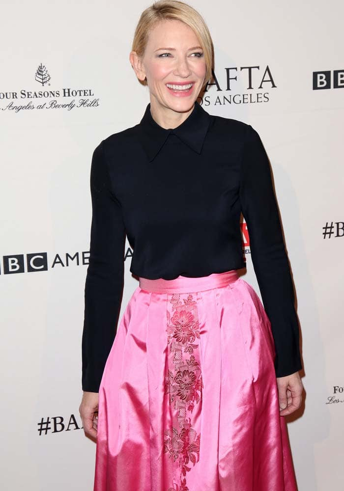 Cate Blanchett smiles while wearing a pink satin skirt