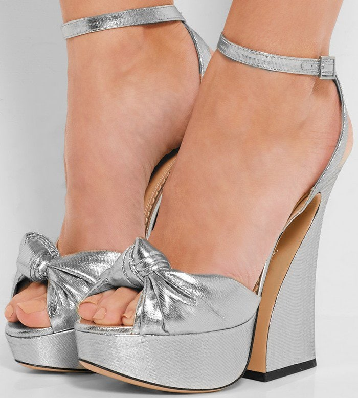 Crafted from sparkling silver lamé, this '70s-inspired pair has a decorative knotted strap and sculpted curved heel