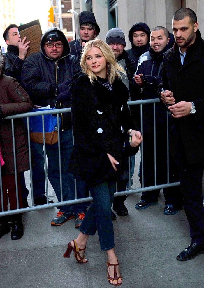 Chloe Grace Moretz wears a black coat over a high-neck top and a pair of three-quarter length jeans
