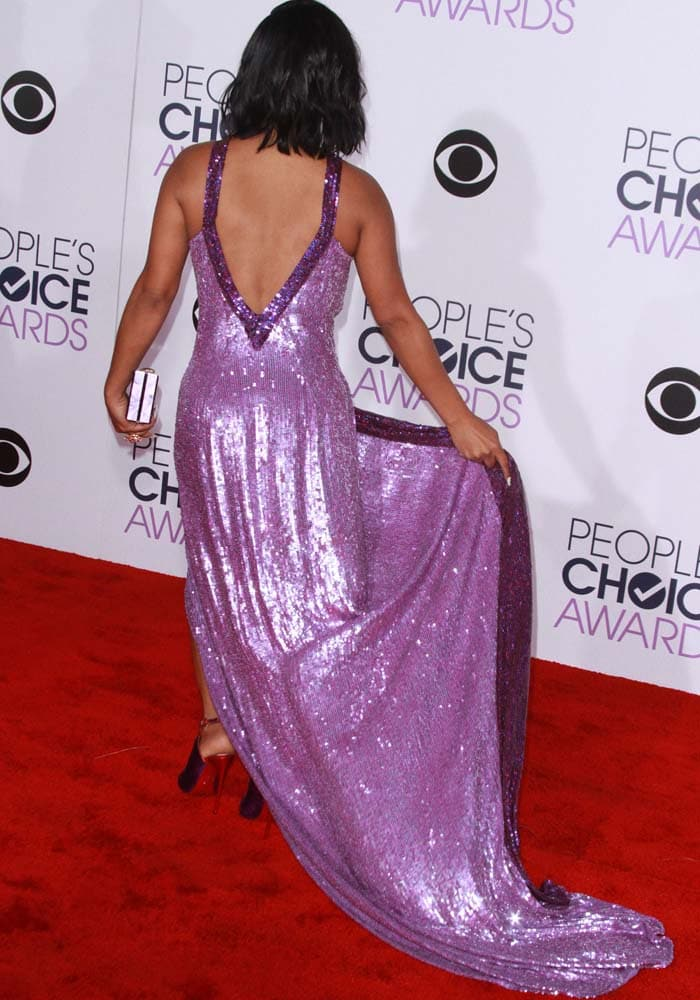 Christina Milian plays with the skirt of her purple sequined dress