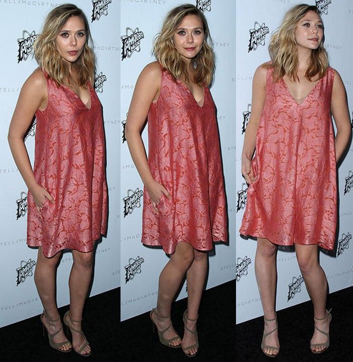 Elizabeth Olsen wears a knee-length salmon-colored dress on the black carpet