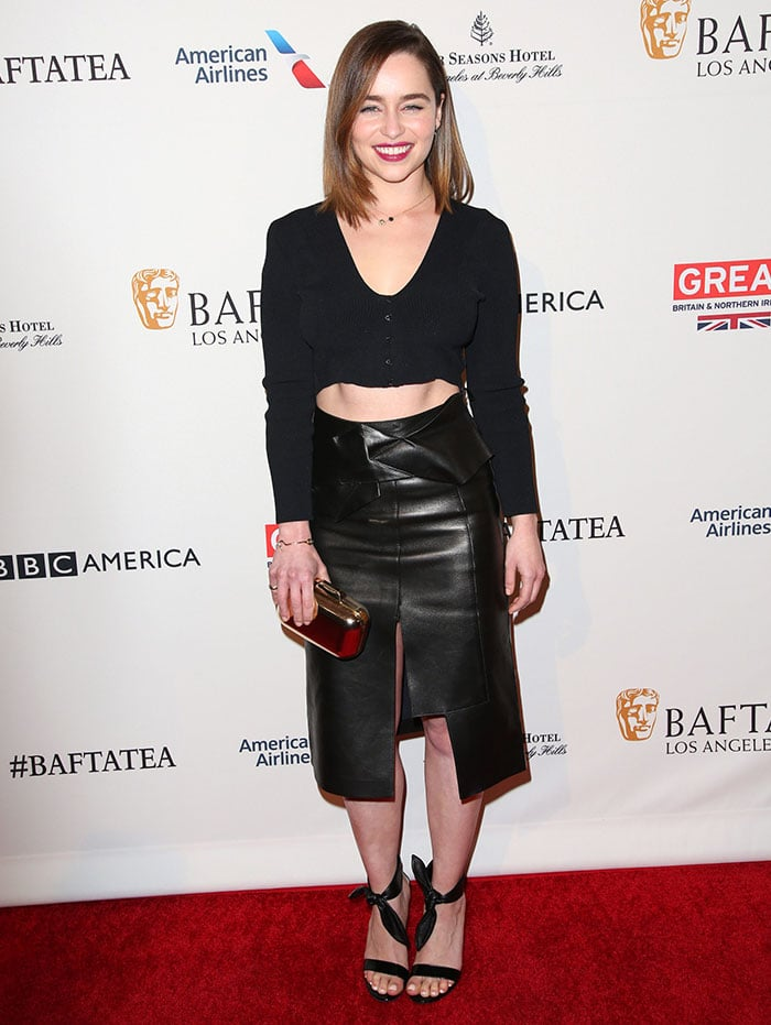 Emilia Clarke flaunted her abs and legs in a knitted long-sleeved crop top and a flirty leather skirt