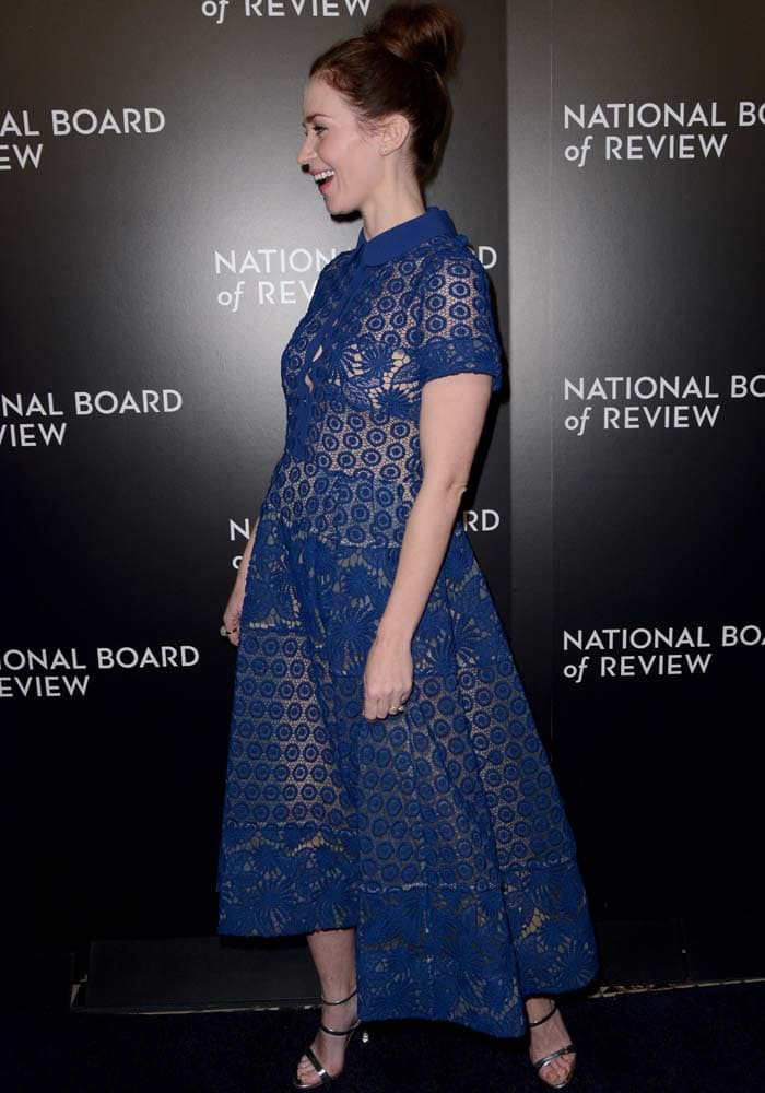 Emily Blunt laughs and shows off the floral pattern of her blue Elie Saab dress