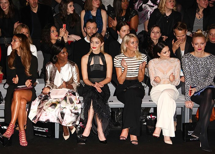 Gigi Hadid sits front row for a fashion show in a Sally LaPointe dress
