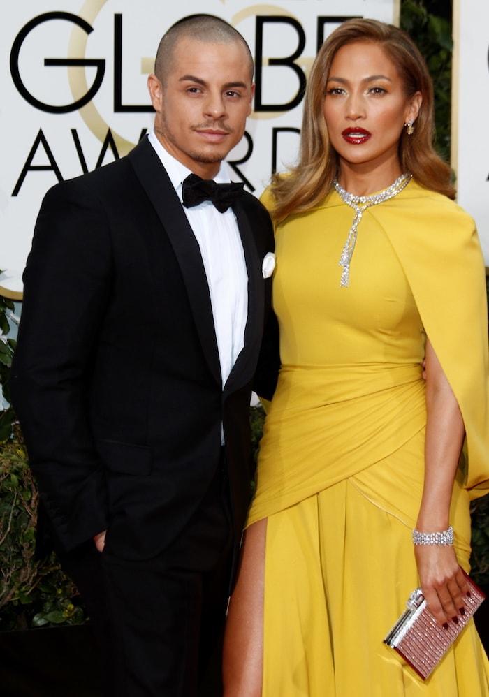 Jennifer Lopez poses with Casper Smart at the Golden Globes in a yellow Giambattista Valli dress