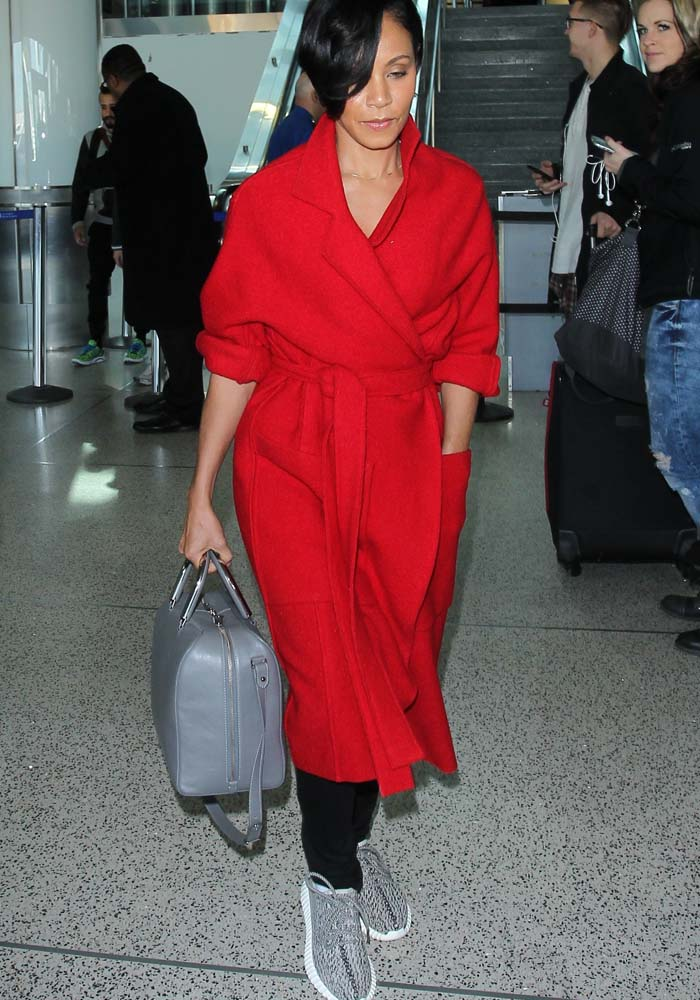 Jada Pinkett-Smith strolls through LAX in a long red trench coat paired with black jeans