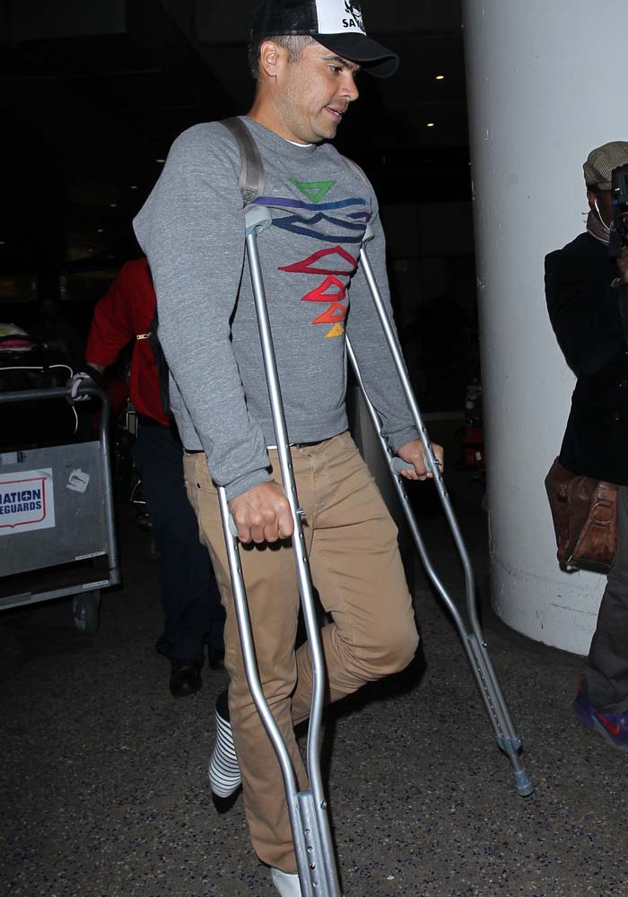 Jessica Alba's husband, Cash Warren, enters LAX on crutches