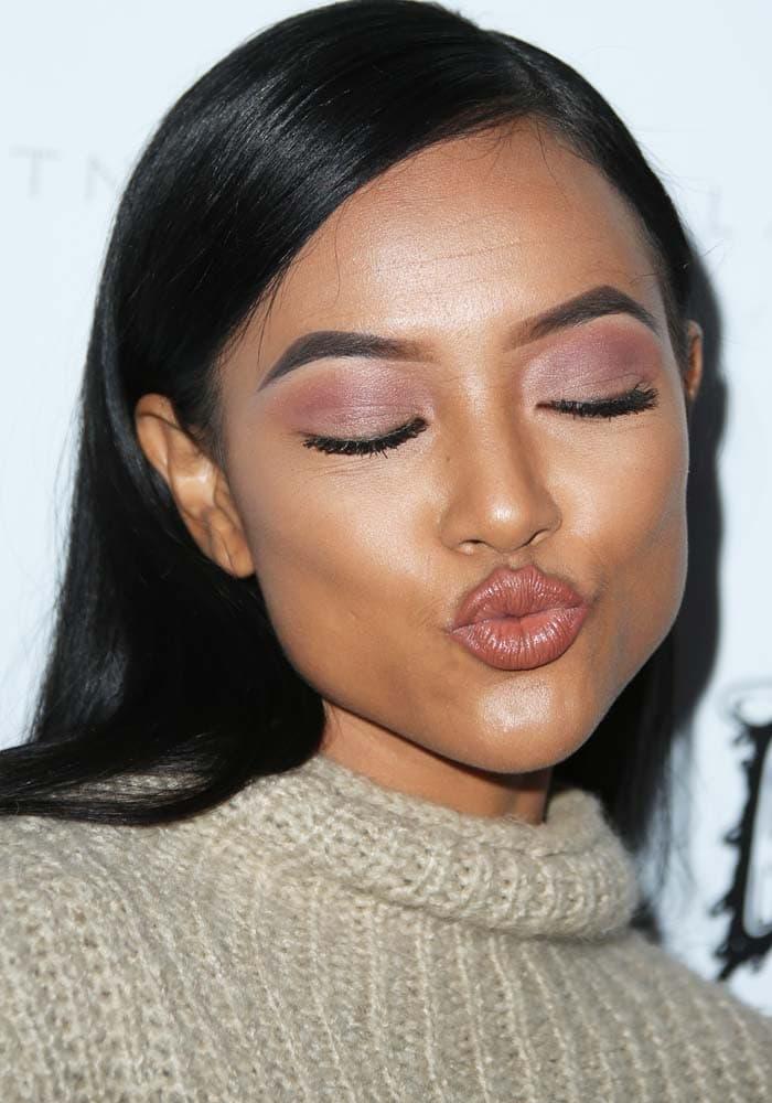 Karrueche Tran shows off her eye makeup as she blows a kiss