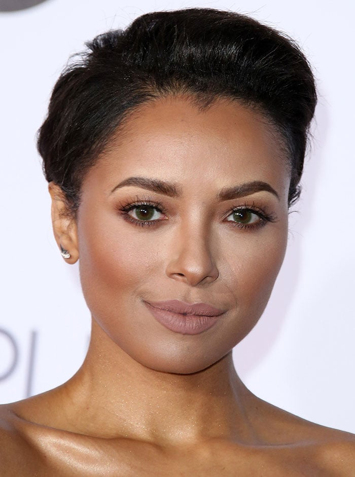 Kat Graham with brushed-back hair and muted makeup