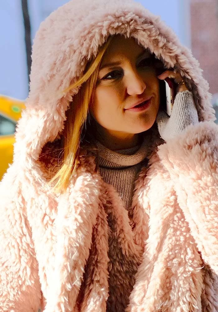 Kate Hudson covers her hair with a furry hood as she returns to her New York hotel