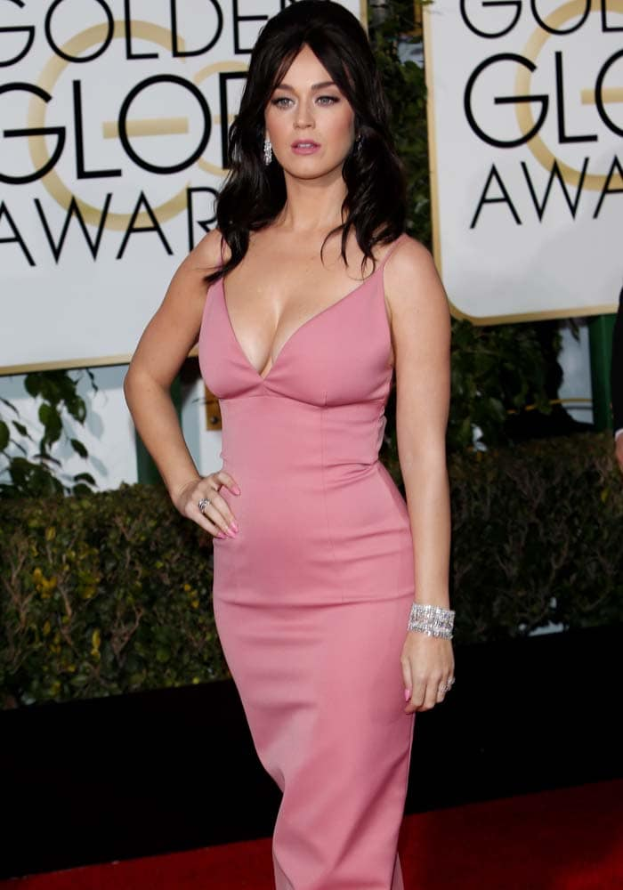 Katy Perry accessorizes with earrings and a bracelet to draw attention to her cleavage in a pink Prada dress