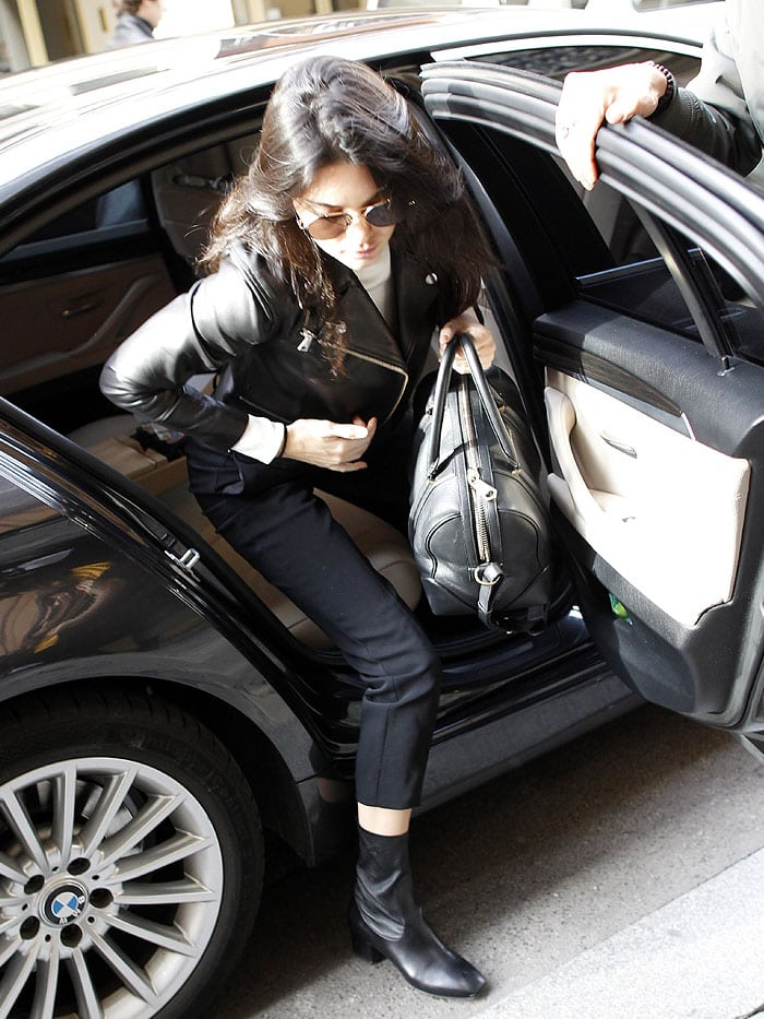 Kendall Jenner holds a Givenchy bag as she steps out of her car during Fashion Week