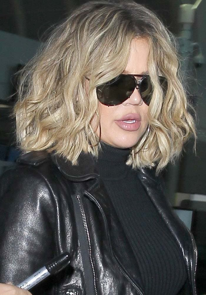 Khloé Kardashian wears her short blonde hair down and messy as she arrives at Los Angeles International Airport