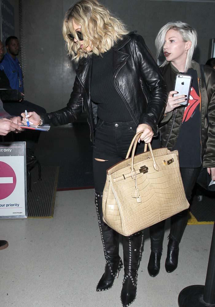 Khloe Kardashian carries a large Hermés tote as she strolls through LAX