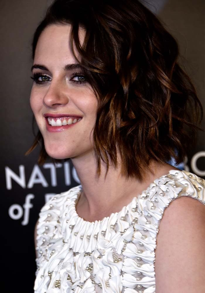 Kristen Stewart smiles in a white-and-pearl-embellished Karl Lagerfeld dress