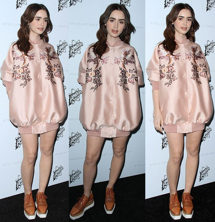 Lily Collins matches her peachy makeup to her pink bomber jacket
