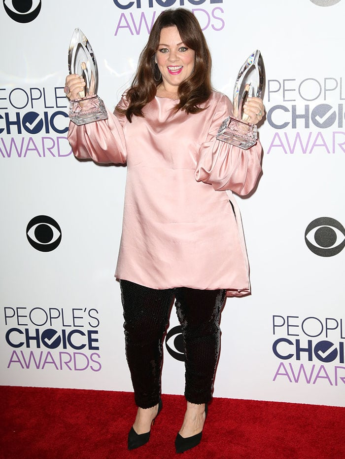 Melissa McCarthy poses with her awards on the red carpet