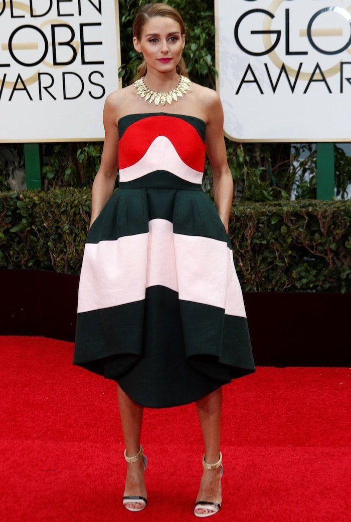Olivia Palermo tucks her hands into the pockets of her red, black and white Delpozo dress