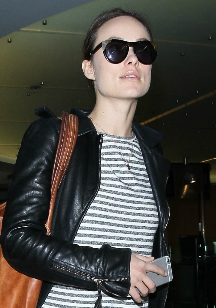 Olivia Wilde covers her eyes with a pair of big sunglasses as she strolls through LAX