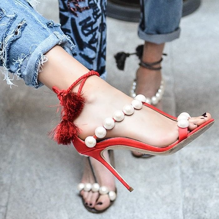 These red stunning heels feature tasseled ankle ties and are embellished with rows of oversized pearls