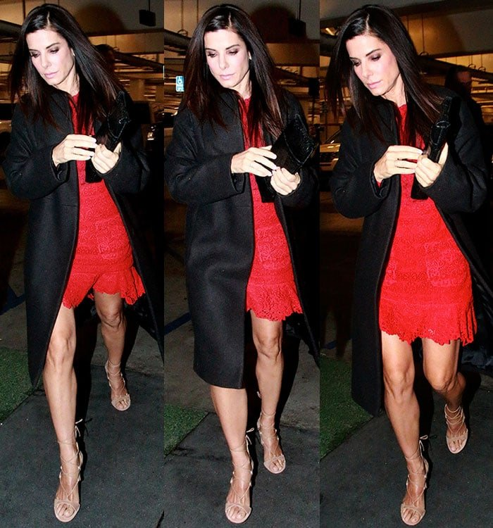 Sandra Bullock covers her red Monique Lhuillier dress with a long black coat