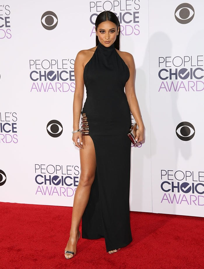 Shay Mitchell accessorized withthree golden hoop earrings, Le Vian bangles, a Casa Reale ring, and a silver Kotur clutch