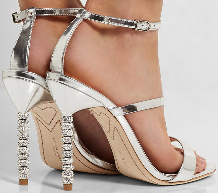 This high-shine silver leather pair is set on a sculptural stiletto heel that's hand-embellished with brilliant crystals