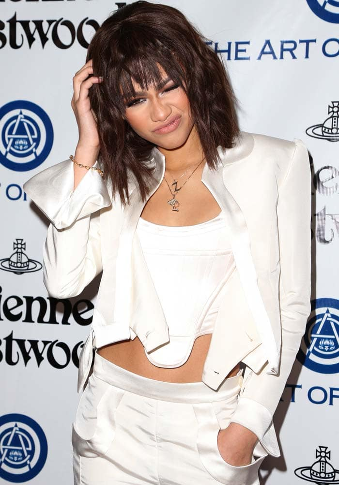 Zendaya accents her two-piece white suit with several personalized necklaces